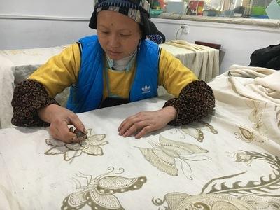 Femme Miao dessinant un motif de batik à la cire